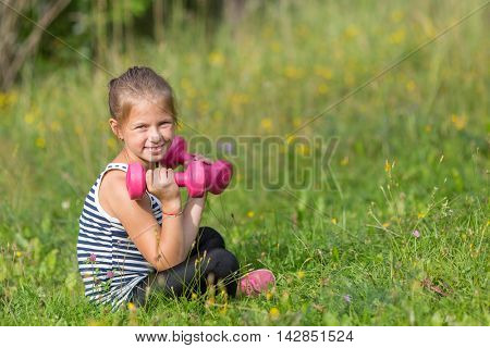 Ten-year-old girl with dumbbells sitting on a green meadow.