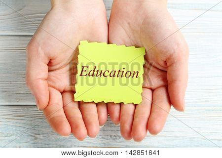 Female hands holding sheet of paper, education