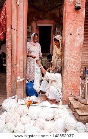 Jaipur India - Jule 29, 2011: Women buying yarn in a street market