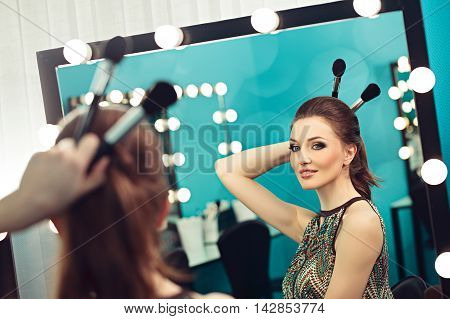 Young beautiful woman joking with make-up brushes in front of a mirror