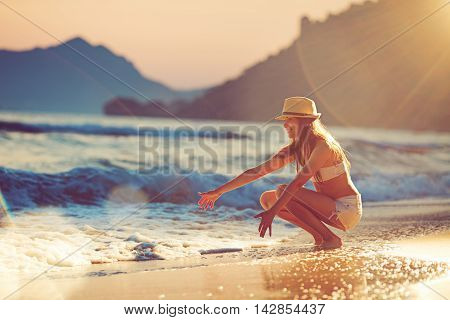 Young beautiful woman sitting in the surf at sunset and stretching her arms to the waves; lens flares backlight