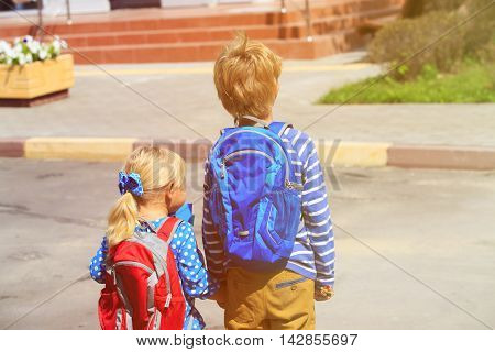 kids go to school- little boy and girl with backpacks near school or daycare building