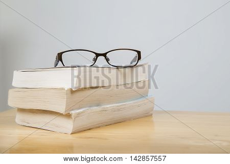 Reading glasses on pile of books on a wooden table