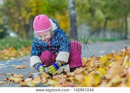 Two years old girl is holding thermos cup hunkering down in autumn foliage covering backdrop