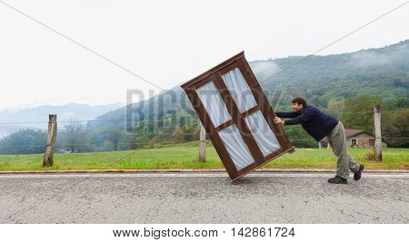 A man pushes a wardrobe along a mountain road