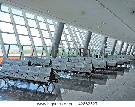 Waiting area at the airport with empty seats and view to the airfield.