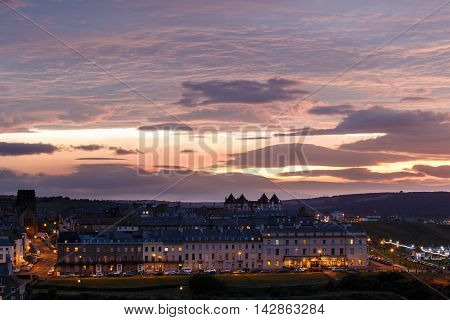 WHITBY ENGLAND - AUGUST 12: Whitby town in the evening against a dramatic sunset. In Whitby North Yorkshire England. On 12th August 2016