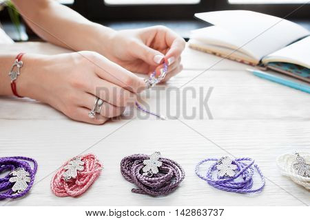 Woman making homemade bracelet. Variety of accessories on white wooden table, artisan workplace. Creation of handmade jewellery. Female leisure home work