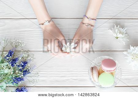 Hands of female florist holding flowers for creating bouquet on white wooden table, flat lay. Top view on workplace of young creative woman with sweets. School of floristry