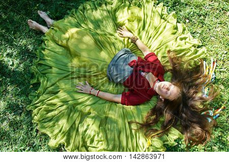 girl with brown hair in a clothes in boho style lies on the grass
