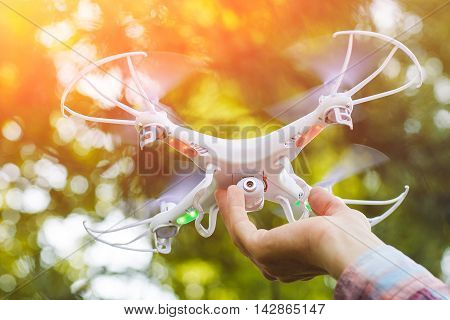 Take of drone flying form hand. Quadrocopter playing in forest. Aeromodelling, innovation, toy, leisure concept