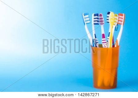 Various toothbrushes in orange cup on blue background with copy-space on the left side.