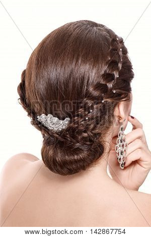 Studio portrait of young beautiful woman with brunette hair and braid hairdo. Rear view. Isolated on white background.