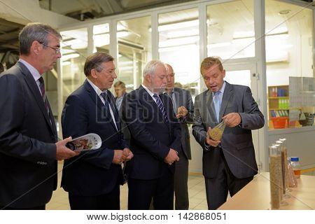 ST. PETERSBURG, RUSSIA - AUGUST 11, 2016: Director of the Heineken brewery Oleg Bokov shows the grains to vice-governor of St. Petersburg Igor Divinsky (center) during his working visit to enterprise