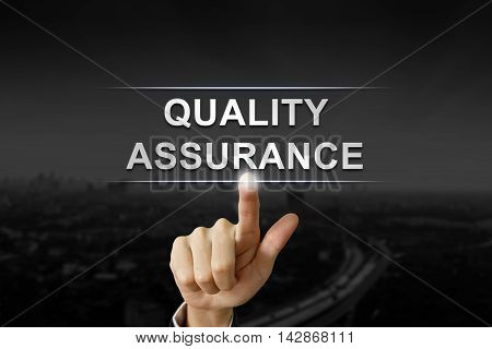 business hand clicking quality assurance button on black blurred background