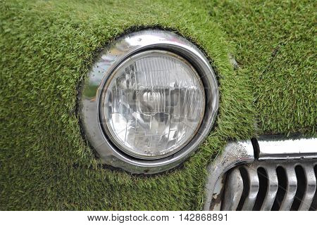 Car covered with artificial grass close-up light Car covered with artificial grass close-up light