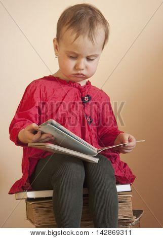 The little girl sitting on the stack of books (education studies self development)