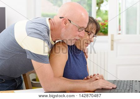 a mature couple with a laptop in home