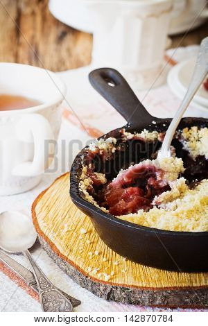 Plum crumble in a frying pan on the table. Traditional English cuisine. Selective focus