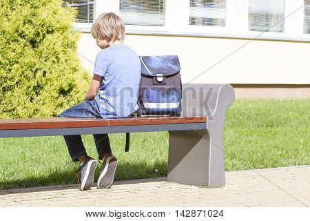 Sad, lonely, unhappy, disappointed boy sitting alone near school. Casual clothes and backpack. Education loneliness feeling concept