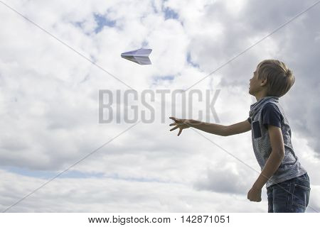 Boy flying a paper plane against blue sky. Low angle view