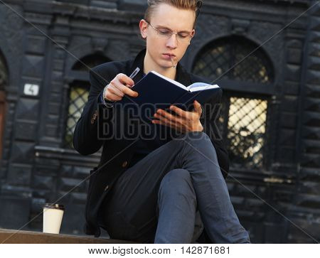 young student smoking and preparing for the exam in old center of europe city Lviv (education knowledge self-development self-improvement)