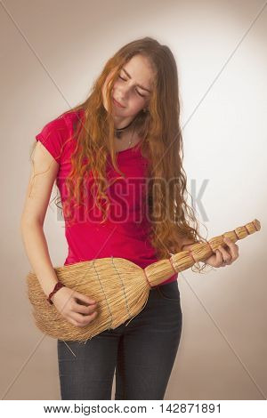woman with a broom styled rock guitarists (humorous photo)