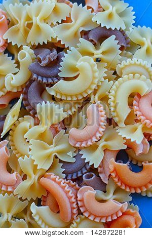 Multicolored different shapes of uncooked pasta in bulk on the table