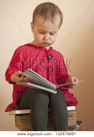 The little girl sitting on the stack of books (education studies self development)