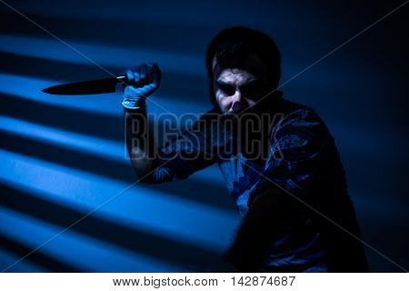 Man Killing a Person with a Knife at Night on Blue Background