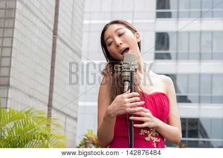 Asian Woman Singing On The Rooftop Of The Building In Outdoor Scene