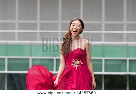 Happy And Smiling Cute Asian Woman Walking In Red Evening Dress