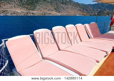 Pink sun beds on a boat in the sea Turkey