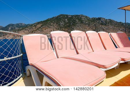 Pink sun beds on a boat in the sea, Turkey