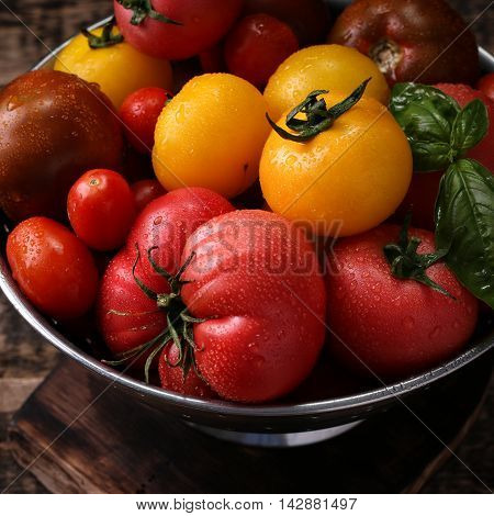 Colorful tomatoes red tomatoes yellow tomatoes orange tomatoes green tomatoes. Tomatoes background. vintage wooden background