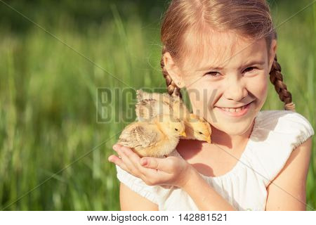 Portrait of little girl with chick outdoors at the day time.