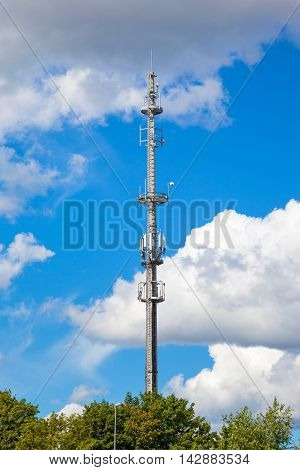Cell tower and radio antenna over blue sky.