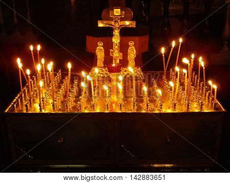 Candles burning before the crucifix in the Church. Christian religious holidays and ceremonies.