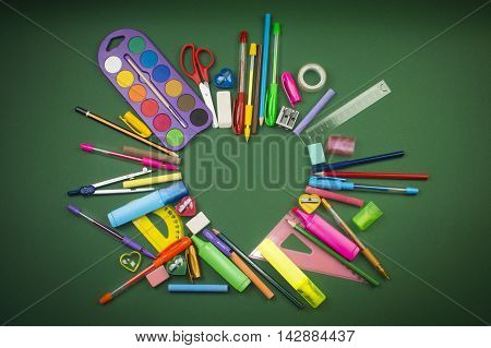Different school supplies in heart shape on green background.