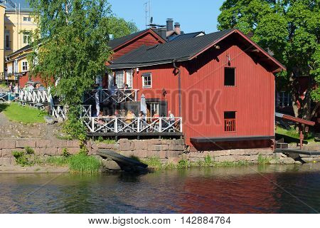 PORVOO, FINLAND - JUNE 13, 2015: Summer cafe in the historic barn on the bank of the river Porvoyoki. Historical landmark of the city Porvoo, Finland