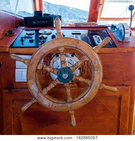 Ship's cabin with instruments and wooden wheel
