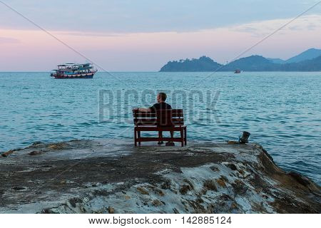 Young man sits lonely at the seaside at dusk.