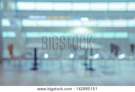 Blurred abstract background of empty cafeteria in University or food court in shopping mall. Blue tone image