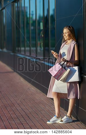 Smiling girl with shopping bags with phone in hand. Shopper. Sales. Concept of woman shopping.