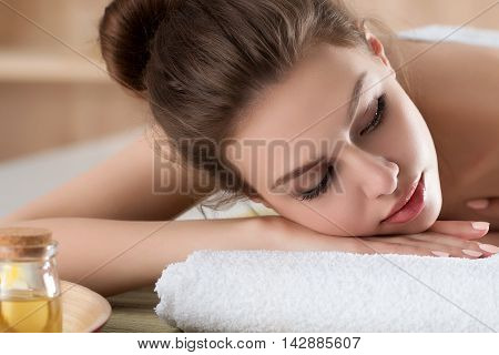 Beautiful young woman lying down at spa salon. Skin and body care healthy lifestyle relaxation massage and cosmetology concept