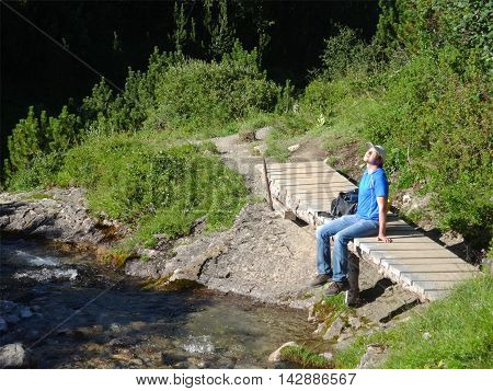 Male hiker rests enjoying the sunshine on his face. He sits on a small wooden bridge next to the Lech river. The trail is the first stage of the Lech hiking trail between the Formarin lake and Lech.