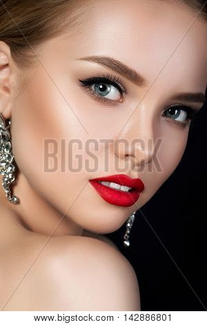 Close up portrait of young beautiful woman with evening make up looking over her shoulder. Red lips and eyeliner. Classic makeup concept. Studio shot.