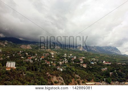panorama of crimean mountains and thick fog over mountains and township on