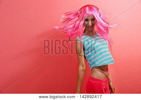 Glamour young woman with headphones on pink background
