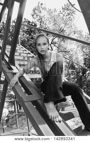 Girl Sitting On An Iron Stairs.